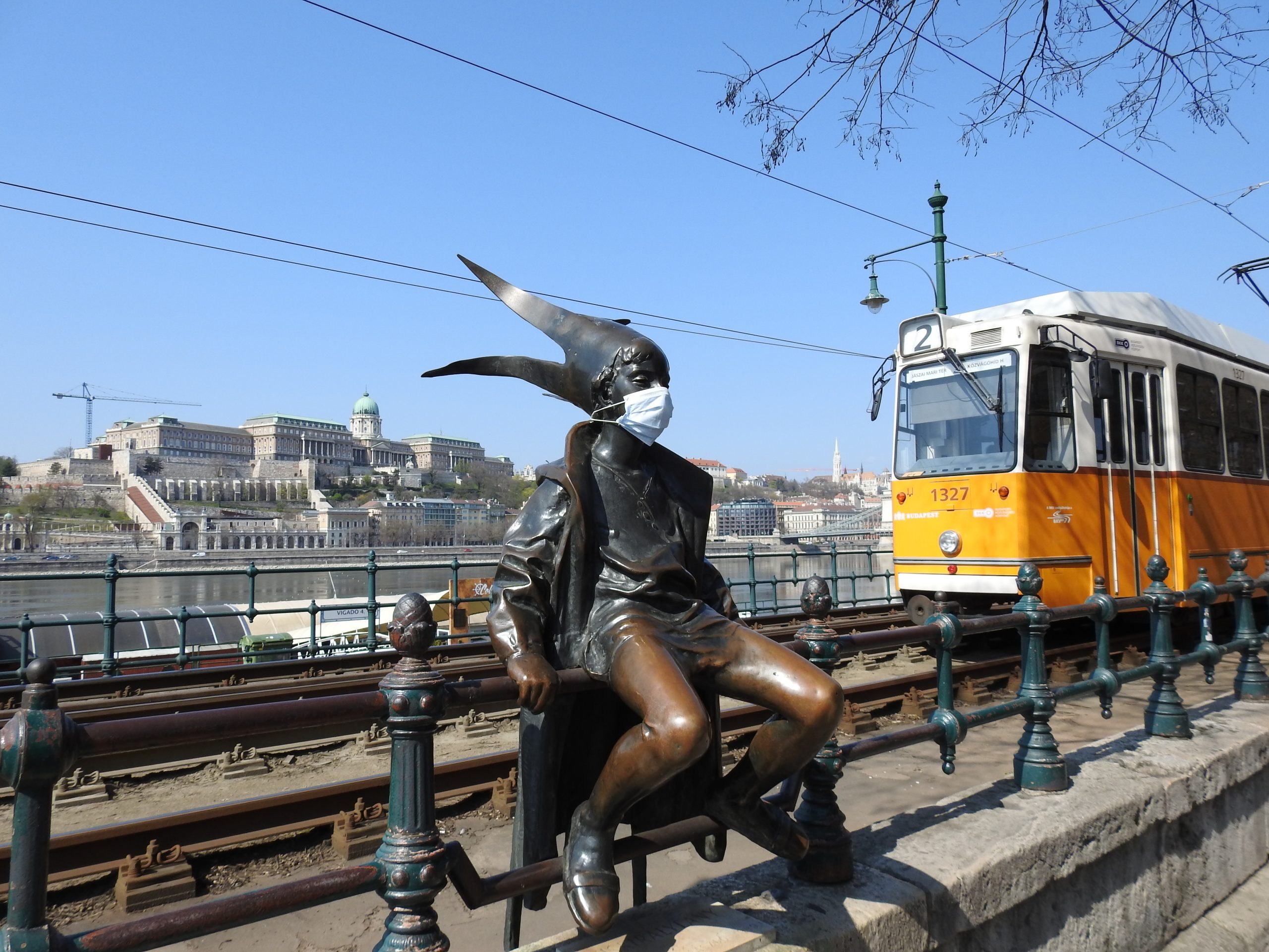 The little Princess statue wearing a mask on the Danube promenade with a tram and the Royal palace in the background
