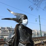 Close photo of the Little Princess statue wearing a mask during times of Covid-19 in Budapest
