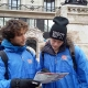A picture taken of two tour guides wearing our royal blue free tour uniforms in wintertime