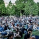 Photo showing a lot of people sitting in the green grass during a festival in the heart of Budapest