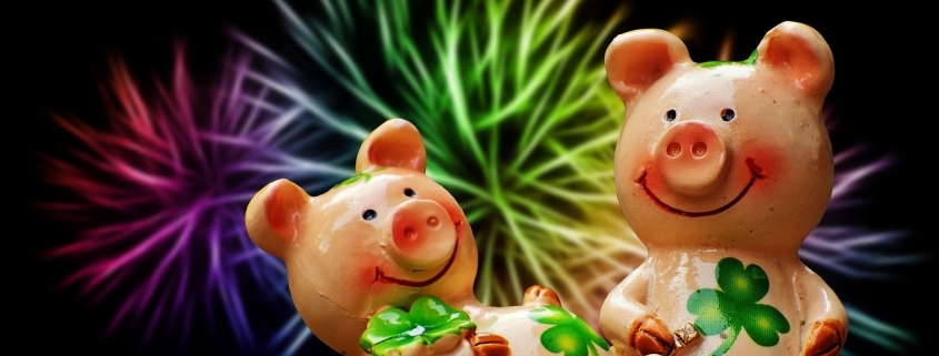 Two pink piglets holding four-leaf clovers that bring luck according to the superstition