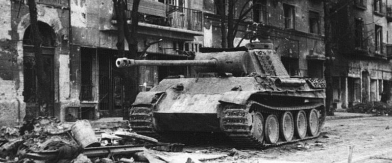 Black and white picture of apartment buildings and a a tank on the streets of the center of Budapest