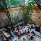 The garden of a popular bar in Budapest with tables, benches, lights and people chatting