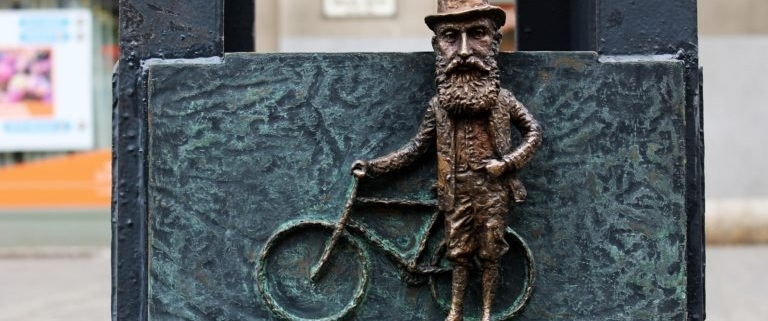 Caption of one of the mini statues of Hungarian sculptor Mihaly Kolodko depicting Theodore Herzl with his bike
