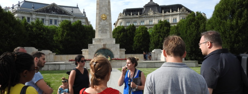 A group with our guide in blue uniform on the Liberty square, in front of the Soviet war memorial of Budapest