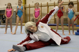 Ágnes Keleti, longest living, oldest Olympic gold medalist of the world performing a split while her pupils watch her