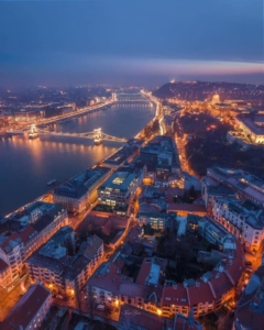 An aerial shot showing Budapest, the river Danube and the Chain bridge lit up on a winter night