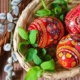 Colorful painted Easter eggs in a basket with some bark next to it