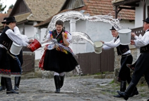 Boys watering a girl dressed in traditional folk clothes at Easter in Hungary